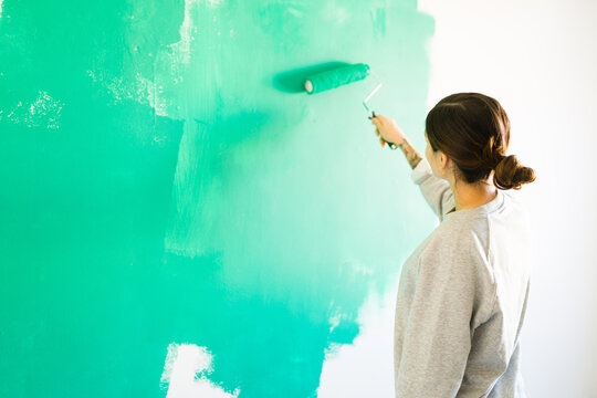 Beautiful woman painting the walls with a paint roller