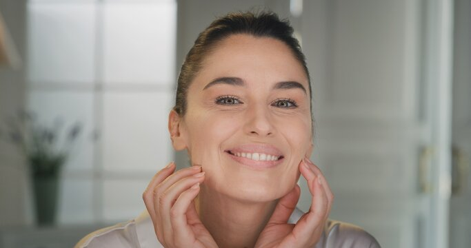 Beauty shot of mature woman with perfect face skin after applying moisturizing cream pampering it gently with fingers to absorb better on golden background. Concept of skincare, cosmetics, healthcare