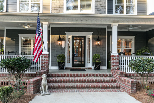 Front door entrance to a large two story blue gray house with wood and vinyl siding and a large American flag.
