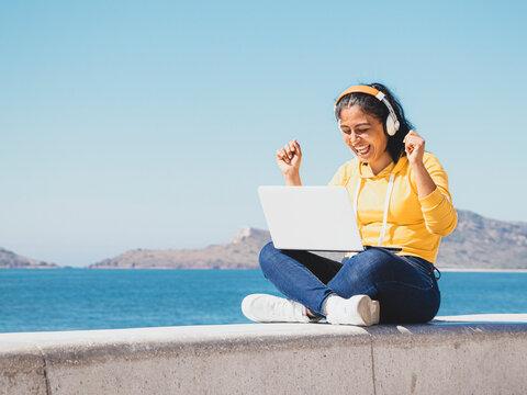Foto Mujer latina joven feliz escuchando música en computadora portátil junto al mar de ropa amarrilla y audífonos