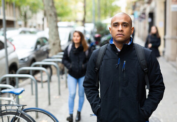 Man in black jacket with backpack walks along a city street. High quality photo Fotobehang