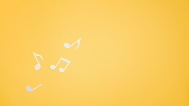 Musical notes cut from paper, flat lay. Top view music layout on yellow background. Place for text