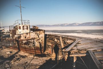 The rusty old ship cemetery stands in the ice of a frozen lake