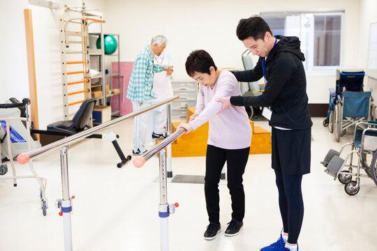 高齢女性の歩行訓練を補助する男性理学療法士