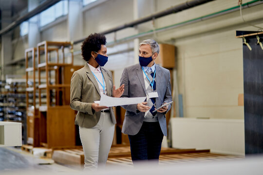 African American businesswoman and her colleague with face masks talking wile walking through woodworking factory.