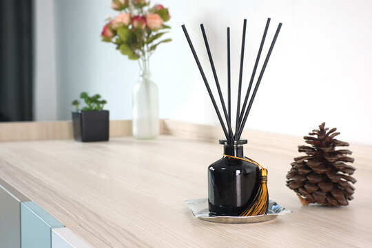 luxury aromatic scent reed diffuser glass bottle is used as room freshener on the wooden table in the bedroom to create romantic and relax ambient with background of the flowers on the valentine day