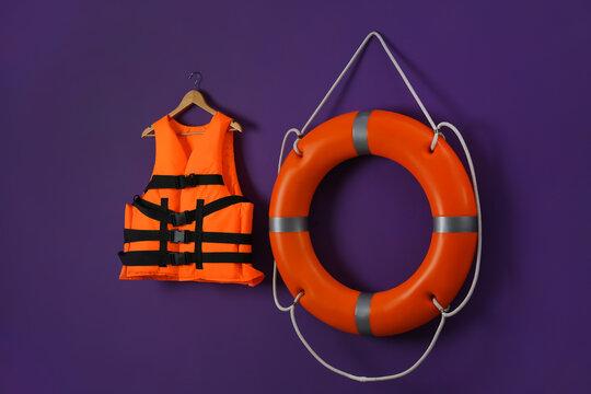 Orange life jacket and lifebuoy on violet background. Rescue equipment