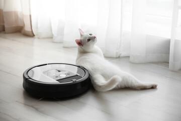 Obraz Modern robotic vacuum cleaner and cute cat on floor indoors - fototapety do salonu