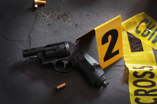 Composition with gun and shell casing on black slate table. Crime scene