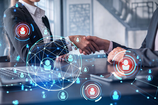 Recruitment concept of hiring of a new talented specialists for international company. Handshake as a concept of agreement to sign an employment contract. Social media hologram icons.