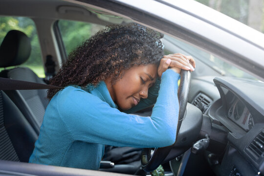 Black is driving a car, she is stressed by heavy traffic.