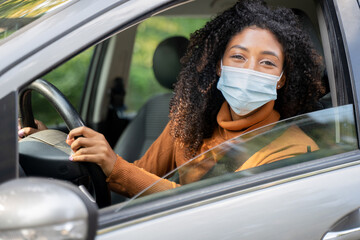 African woman with curly hair with face mask on sitting and driving car. Prevention from spreading corona virus