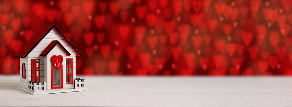 . Toy wooden house, on a bokeh background in the form of a heart. Valentine's Day holiday concept.