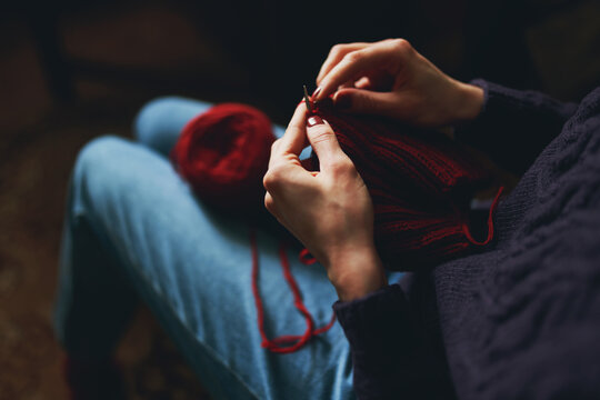 Female hands knitting with red yarn.