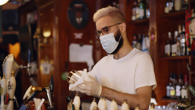 Bartender wearing face mask and gloves cleaning empty glass