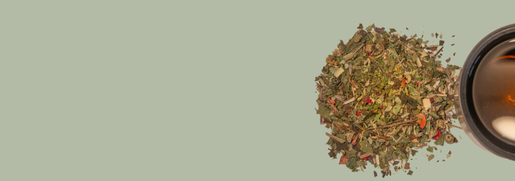 Banner with pile of healthy herbs near a cup of herb tea isolated at solid green background with copy space. Concept healthy diet, supplements, and food
