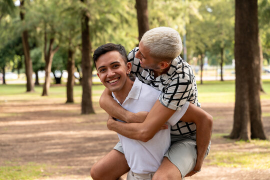 Young gay guy giving a piggyback ride in a public park