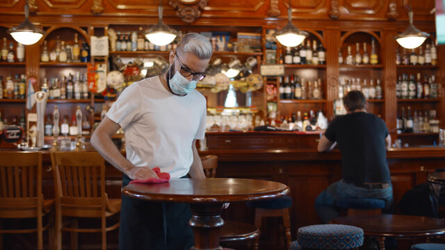 Waiter wearing protection face mask in apron cleaning table with disinfectant spray