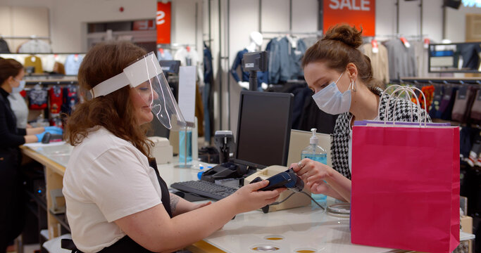 Woman in safety mask at checkout in fashion store paying with credit card.