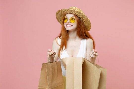 Young smiling redhead ginger caucasian woman 20s wear straw hat glasses summer clothes holding package bags with purchases after shopping look aside isolated on pastel pink background studio portrait.