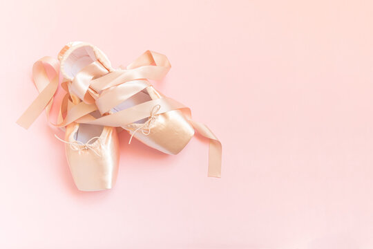 New pastel beige ballet shoes with satin ribbon isolated on pink background. Ballerina classical pointe shoes for dance training. Ballet school concept. Top view flat lay, copy space