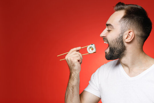 Funny young bearded man 20s wearing casual white t-shirt eating hold in hand sticks chopsticks with makizushi sushi roll traditional japanese food isolated on red color background studio portrait.