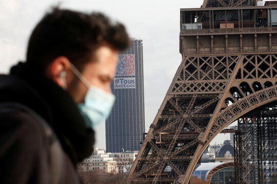 People wear protective face masks in Paris