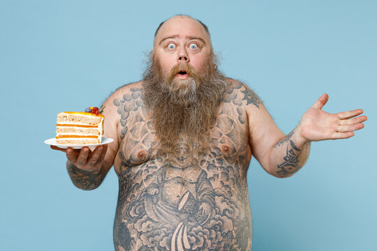 Shocked fat pudge obese chubby overweight man has tattooed naked big belly hold sweet cake spreading hands isolated on blue background studio portrait. Weight loss obesity unhealthy diet concept.