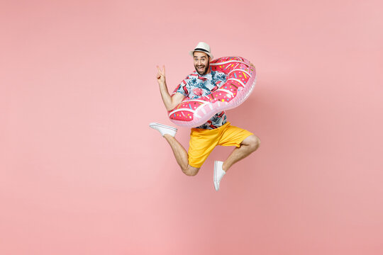 Full length funny traveler tourist man in summer clothes hat jumping hold inflatable ring showing victory sign isolated on pink background. Passenger traveling on weekends. Air flight journey concept.