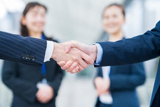 握手を見守るビジネスウーマン
