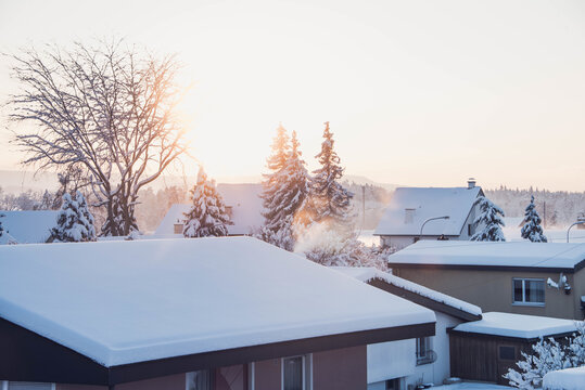 Beautiful view of houses with snow on the roof at scenic sunset
