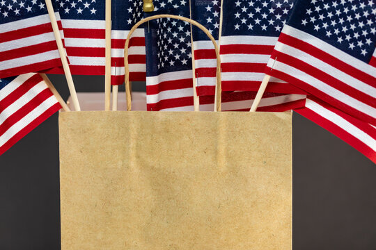 American flags in a brown paper bag for advertisement of sales.