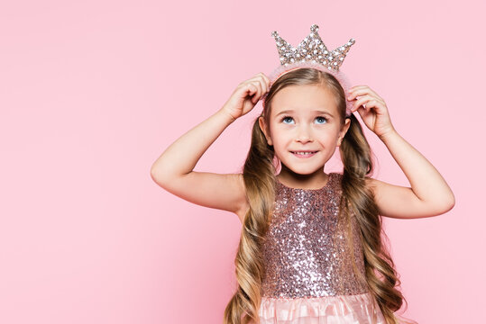 cheerful little girl in dress adjusting crown isolated on pink