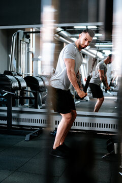 bodybuilding details and fitness workout. Man in sport gear working out arms at gym