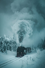 The famous Brocken train with steam in the winter mountain landscape with heavy fog and mystic vibes. Steam historic train, Brockenbahn, up the snow hill. Brocken, Harz National Park in Germany