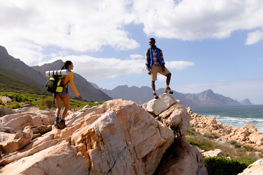 Fit afrcan american couple wearing backpacks hiking on the coast