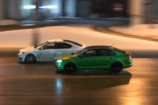 Two cars in motion on city street at night. Racing at high speed on public road. White and green sedans drive on wet winter road