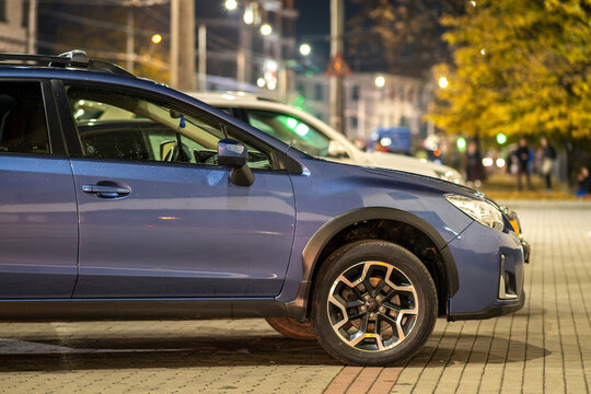Ivano-Frankivsk, Ukraine - November 14, 2020: Blue Subaru Crosstrek car parked on brightly illuminated city street at night.