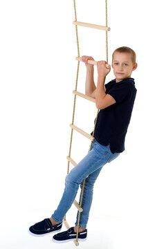 Teenage boy climbiing on rope ladder