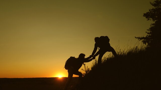 Teamwork silhouette of a group of hikers lends a helping hand in climbing mountains, hill. Uristy climb mountain at sunset, holding hands. Tourists teamwork, climb to top and shake hands with friend.