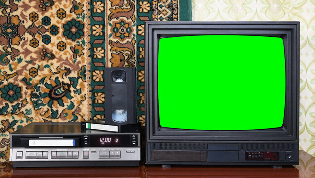 Old black vintage TV with green screen to add new images to the screen, VCR on wallpaper background.