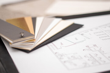 Obraz Interior designer's working table, an architectural plan of the house, a color palette, furniture and fabric samples. Drawings and plans for house decoration. - fototapety do salonu