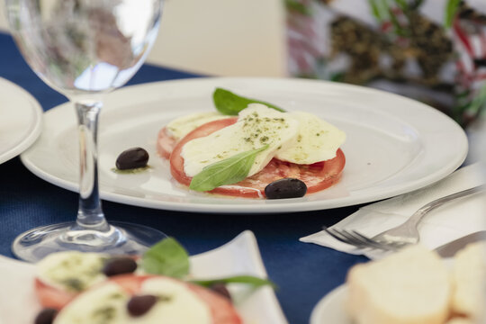 Selective focus shot of a dish made with tomato slices, olives, cheese, and basil leaves