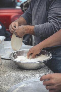 Vertical selective focus shot of a male cook preparing pizza dough