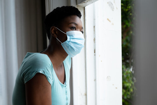 Portrait of african american woman wearing face mask looking out of the window at home