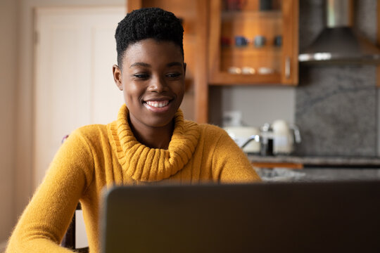 African american woman wearing using laptop and smiling in kitchen