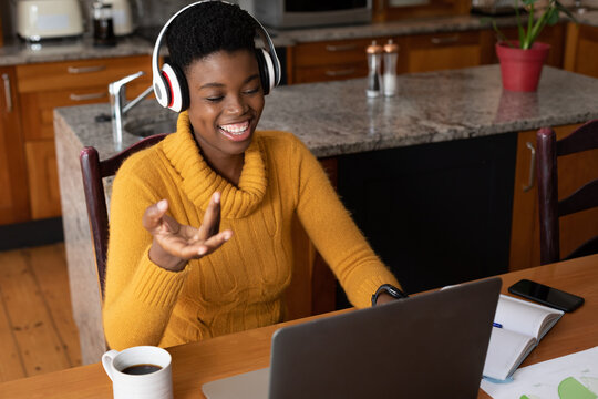 African american woman wearing headphones making video call using laptop in kitchen