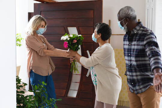 Senior african american couple greeting senior caucasian couple all wearing face masks at home