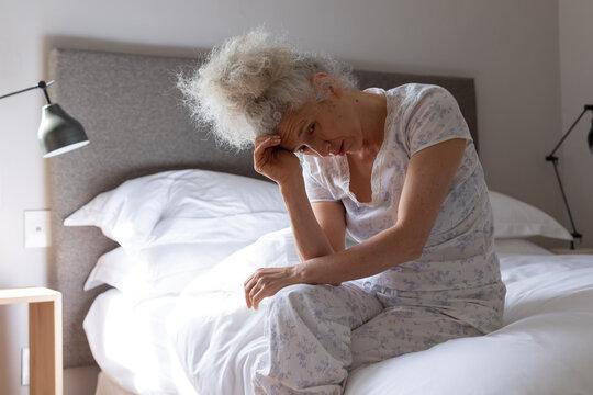 Senior caucasian woman feeling weak sitting on bed