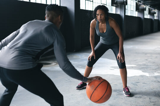 African american man and woman standing in an empty urban building and playing basketball